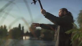 O homem farpado está pescando no banco de rio Pesca do pescador com uma vara de pesca no rio Pesca do rio Movimento lento video estoque