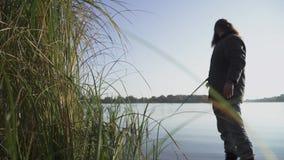 O homem farpado está pescando no banco de rio O pescador está tentando obter peixes, mas escapa Pesca do rio filme