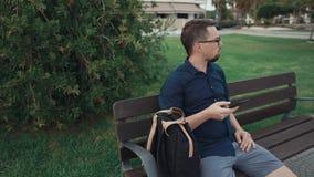 O homem farpado está relaxando no banco no dia, consultando no smartphone filme