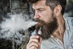 O homem farpado fuma o vape, nuvens de fumo brancas Conceito eletrônico do cigarro O homem com barba longa olha relaxado Homem imagem de stock royalty free