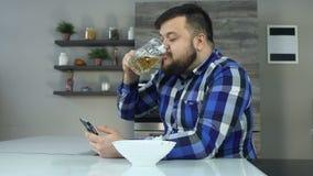 O homem farpado gordo de Timelapse bebe a cerveja, come microplaquetas e olha o feed noticioso no smartphone Ressacas grossas do  video estoque