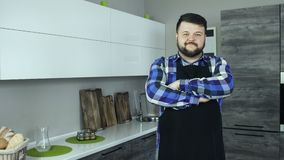 O homem farpado grosso como um avental vestindo do cozinheiro está em uma cozinha moderna e em olhares na câmera video estoque