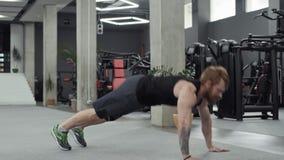 O homem farpado muscular faz impulso-UPS no gym Fazer do homem levanta o exercício no Gym vídeos de arquivo
