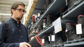 O homem farpado novo com vidros está escolhendo botas em uma loja video estoque