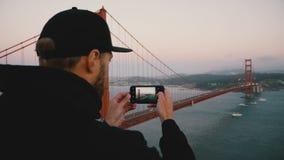 O homem farpado novo da vista traseira no hoodie e no tampão pretos toma a foto do smartphone do por do sol golden gate bridge Sa video estoque