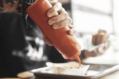 O homem farpado novo do moderno derrama a ketchup em batatas fritas perto acima imagens de stock