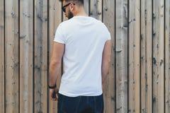 O homem farpado novo do moderno vestido no t-shirt e nos óculos de sol brancos é suportes exteriores contra a parede de madeira Z Fotos de Stock Royalty Free