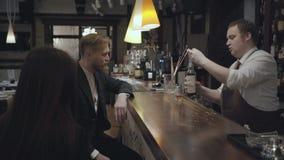 O homem farpado novo e a mulher moreno irreconhecível que sentam-se no contador da barra Álcool de derramamento do barman gordo d vídeos de arquivo