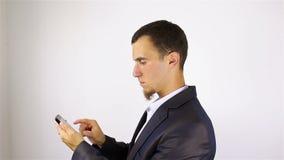 O homem farpado novo entrega os sms da escrita, texting no smartphone video estoque