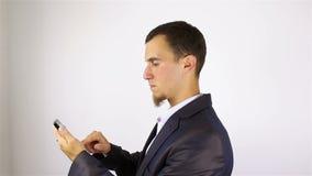 O homem farpado novo entrega os sms da escrita, texting no smartphone vídeos de arquivo