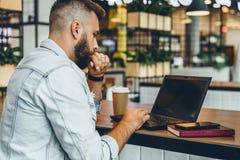 O homem farpado novo está sentando-se no café, datilografando no portátil O Blogger trabalha na casa do café O indivíduo verifica foto de stock