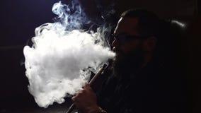 O homem farpado novo nos vidros fuma um cachimbo de água e funde para fora o close up do fumo no fundo preto no movimento lento e video estoque