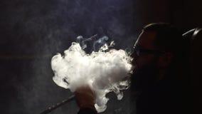 O homem farpado novo nos vidros fuma um cachimbo de água e funde para fora o close up do fumo no fundo preto no movimento lento e vídeos de arquivo