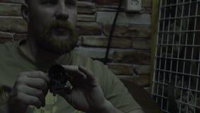 O homem farpado olha com o espaço Homem calvo com uma barba que senta-se na vista do sofá e dos grupos vídeos de arquivo