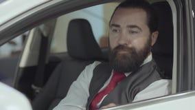 O homem farpado seguro atrativo do retrato que senta-se no veículo e inspeciona comprou recentemente auto do carro video estoque