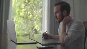 O homem farpado seguro tira usando a tabuleta gráfica que olha em um portátil Mão masculina que tira a produção da animação 3d filme