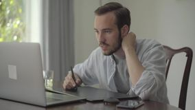 O homem farpado seguro tira usando a tabuleta gráfica que olha em um portátil Mão masculina que tira a produção da animação 3d video estoque