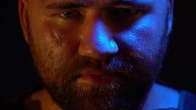 O homem farpado suado com uma barba e uma cicatriz em seu mordente está olhando seriamente a câmera video estoque