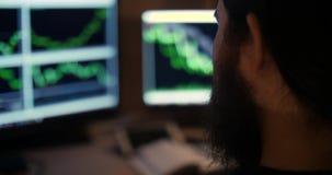O homem farpado trabalha com cartas no close up de 2 monitores filme
