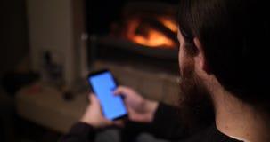 O homem farpado usa um smartphone perto da chaminé video estoque