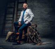 O homem farpado vestido no calças de brim, o revestimento branco e o laço senta o fotografia de stock royalty free