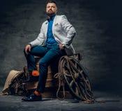 O homem farpado vestido no calças de brim, o revestimento branco e o laço senta o imagens de stock royalty free
