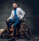 O homem farpado vestido no calças de brim, o revestimento branco e o laço senta o foto de stock