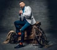 O homem farpado vestido no calças de brim, o revestimento branco e o laço senta o imagem de stock