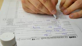 O homem fatigante nervoso está escrevendo contribui a informação no formulário de declaração de rendimentos individual 1040 da re filme