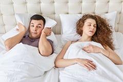 O homem fatigante sofre da insônia, mantém o descanso na cabeça quando ouvir wifes ressonar durante a noite, sono junto em uma ca imagens de stock royalty free