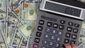 O homem faz cálculos do dinheiro em uma calculadora video estoque