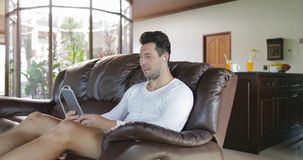 O homem faz a chamada video em linha usando a sala de Sit On Coach In Living do tablet pc, Guy Speaking Internet de sorriso video estoque