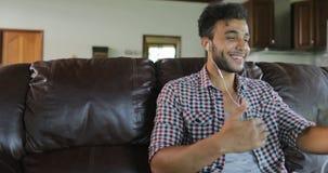 O homem faz a chamada video em linha usando a sala de Sit On Coach In Living do tablet pc, latim Guy Speaking Internet Communicat filme
