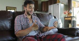 O homem faz a chamada video em linha usando a sala de Sit On Coach In Living do tablet pc, latim Guy Speaking Internet Communicat video estoque