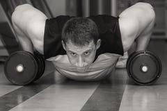 O homem faz exercícios com pesos imagens de stock