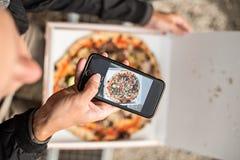 O homem faz a foto da pizza na caixa imagem de stock royalty free