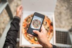 O homem faz a foto da pizza na caixa fotos de stock