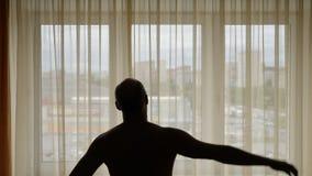 O homem faz a inclinação do exercício para tomar partido dentro seu corpo Equipa a silhueta na janela dianteira Tiro da zorra do  filme