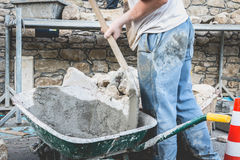 O homem faz o concreto em um carrinho de mão em um local da renovação Imagem de Stock Royalty Free