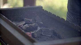 O homem faz o fogo para um assado O homem infla o fogo Carvões em um soldador O homem para balançar uma pá sobre carvões E vídeos de arquivo