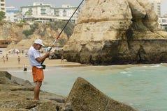 O homem faz a pesca na praia da Dinamarca Rocha do Praia em Portimao, Portugal Fotografia de Stock