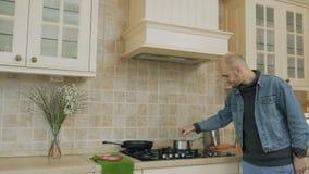 O homem faz um fogo menor no fogão para a sopa vídeos de arquivo