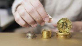 O homem faz umas pilhas das moedas, suportes do bitcoin que inclinam-se na pilha vídeos de arquivo