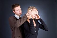 O homem fecha as mãos atrás de um olho da menina. Foto de Stock Royalty Free