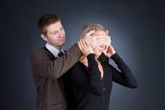 O homem fecha as mãos atrás de um olho da menina. Fotos de Stock Royalty Free
