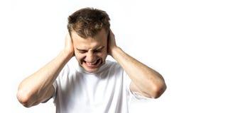 O homem fecha suas orelhas com suas mãos, não quer ouvir qualquer coisa, ruído demasiado alto, dor nas orelhas, em um isolat bran imagens de stock royalty free