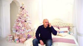 O homem felicita parentes no telefone com feriados do ` s do ano novo com os filhos, sentando-se na cama no quarto com festivo filme