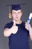 Homem feliz da graduação com polegares do diploma acima sobre o cinza fotos de stock