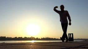 O homem feliz deixa cair uma bola em um banco de rio no por do sol no slo-mo vídeos de arquivo