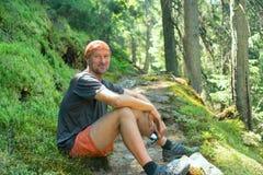 O homem feliz do caminhante é descansar, sentando-se na rota com receiv de GPS foto de stock
